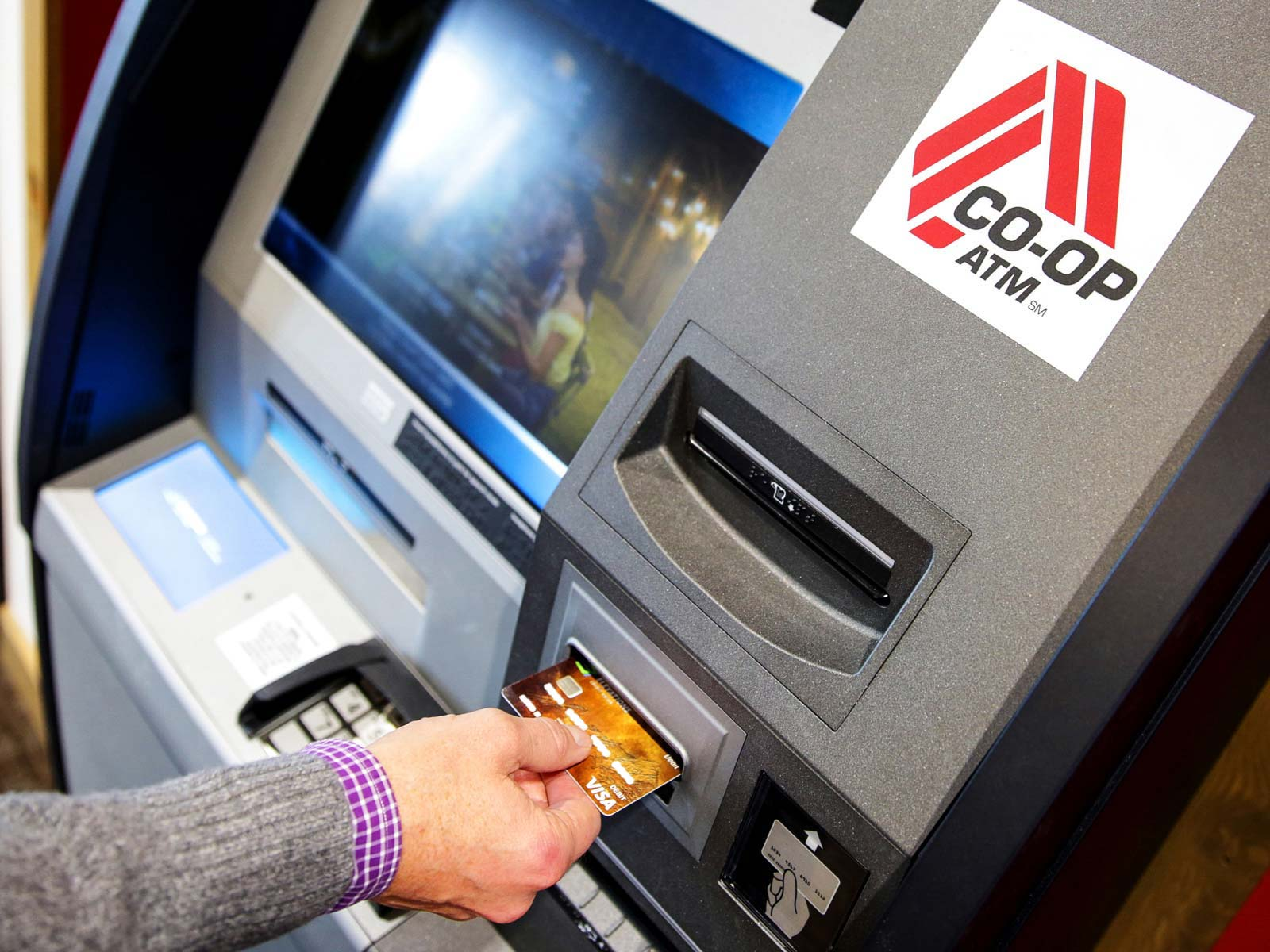Man inserts bank card into Co-Op ATM
