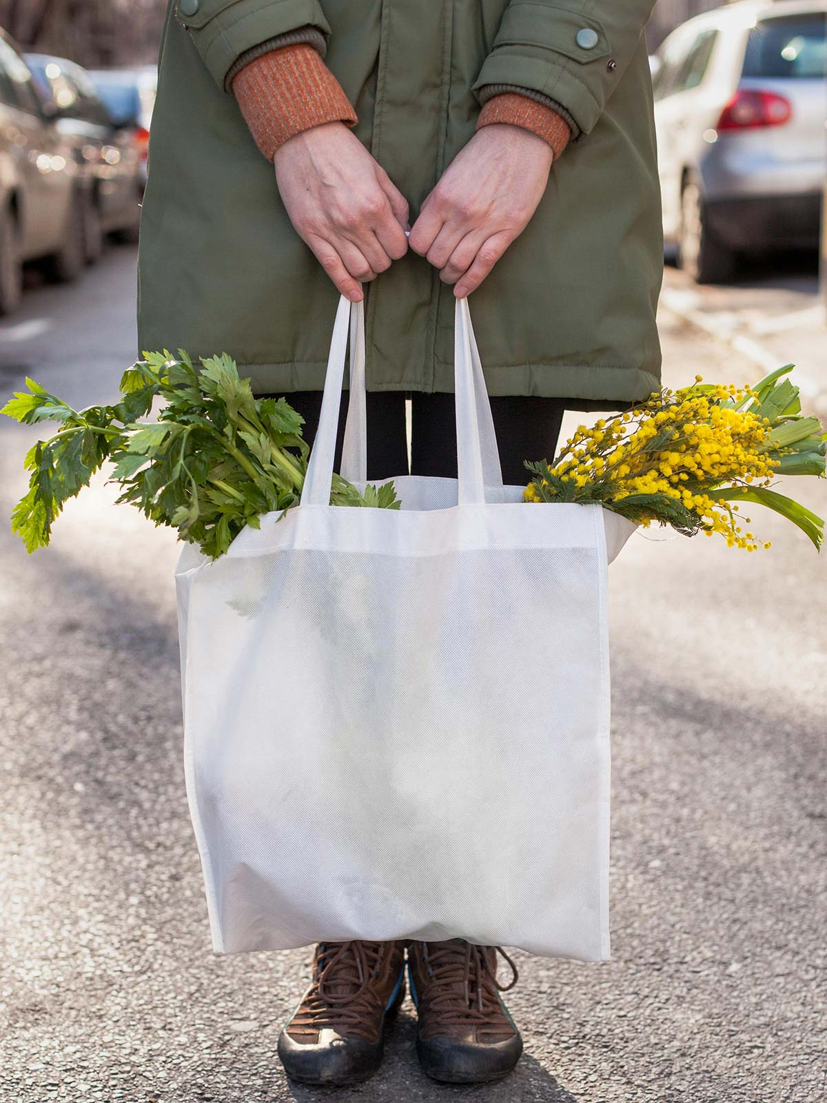 A woman standing in the street with focus on a bag of vegetables and flowers