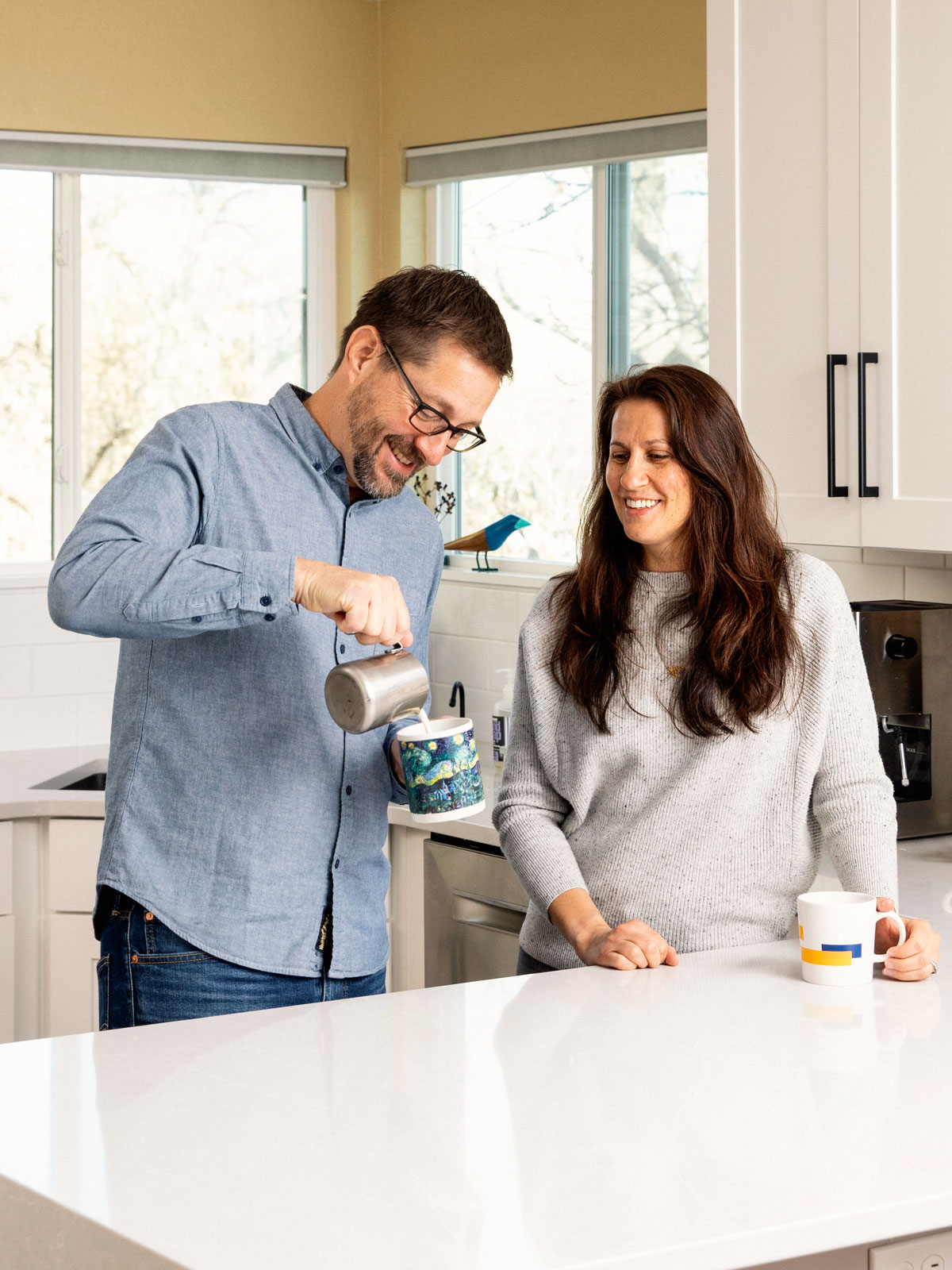 Vertical image of Man and woman making coffee in a renovated kitchen