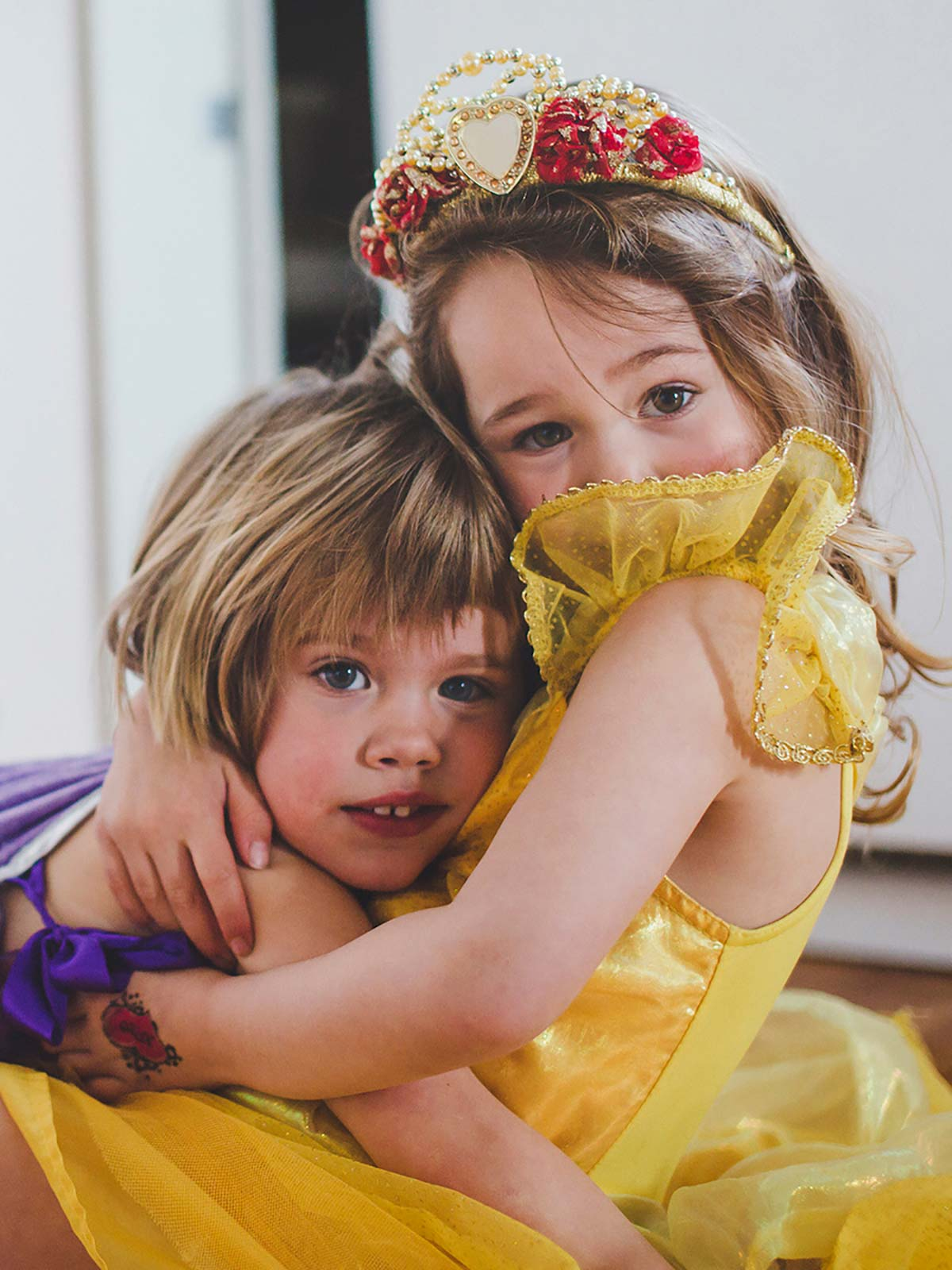 Two little girls dressed in princess costumes hug in their new home