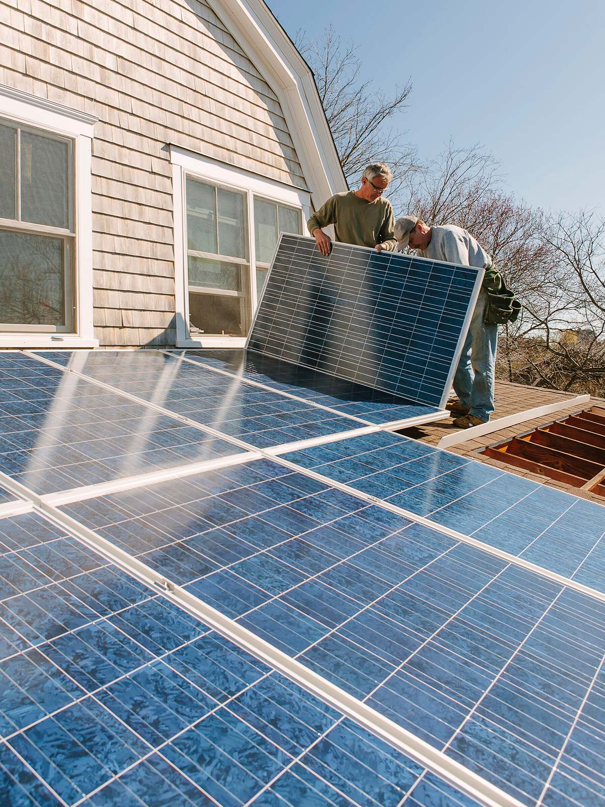 Two male contractors on a roof of a home, installing solar panels