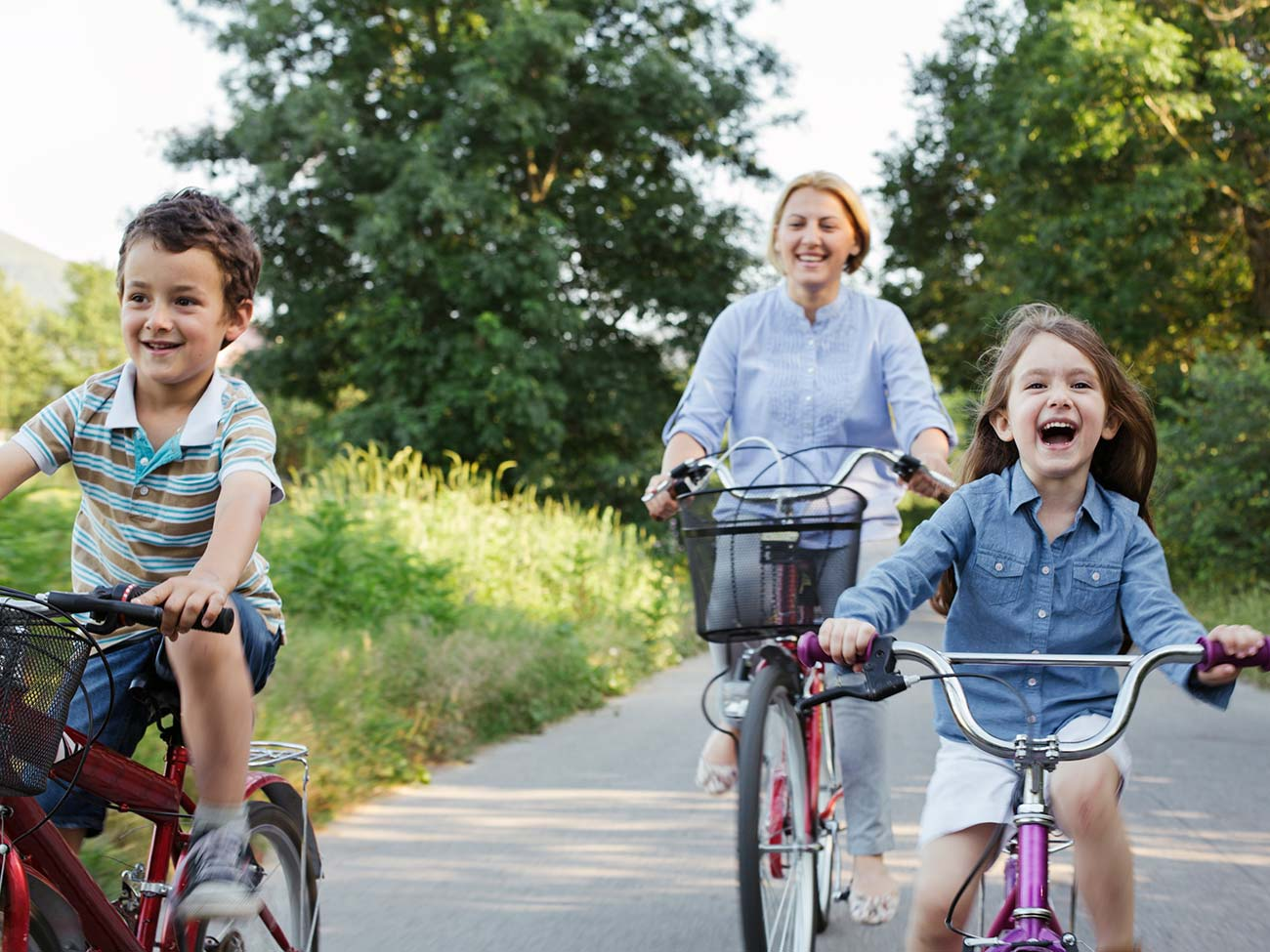 Mother and two children riding bikes and laughing