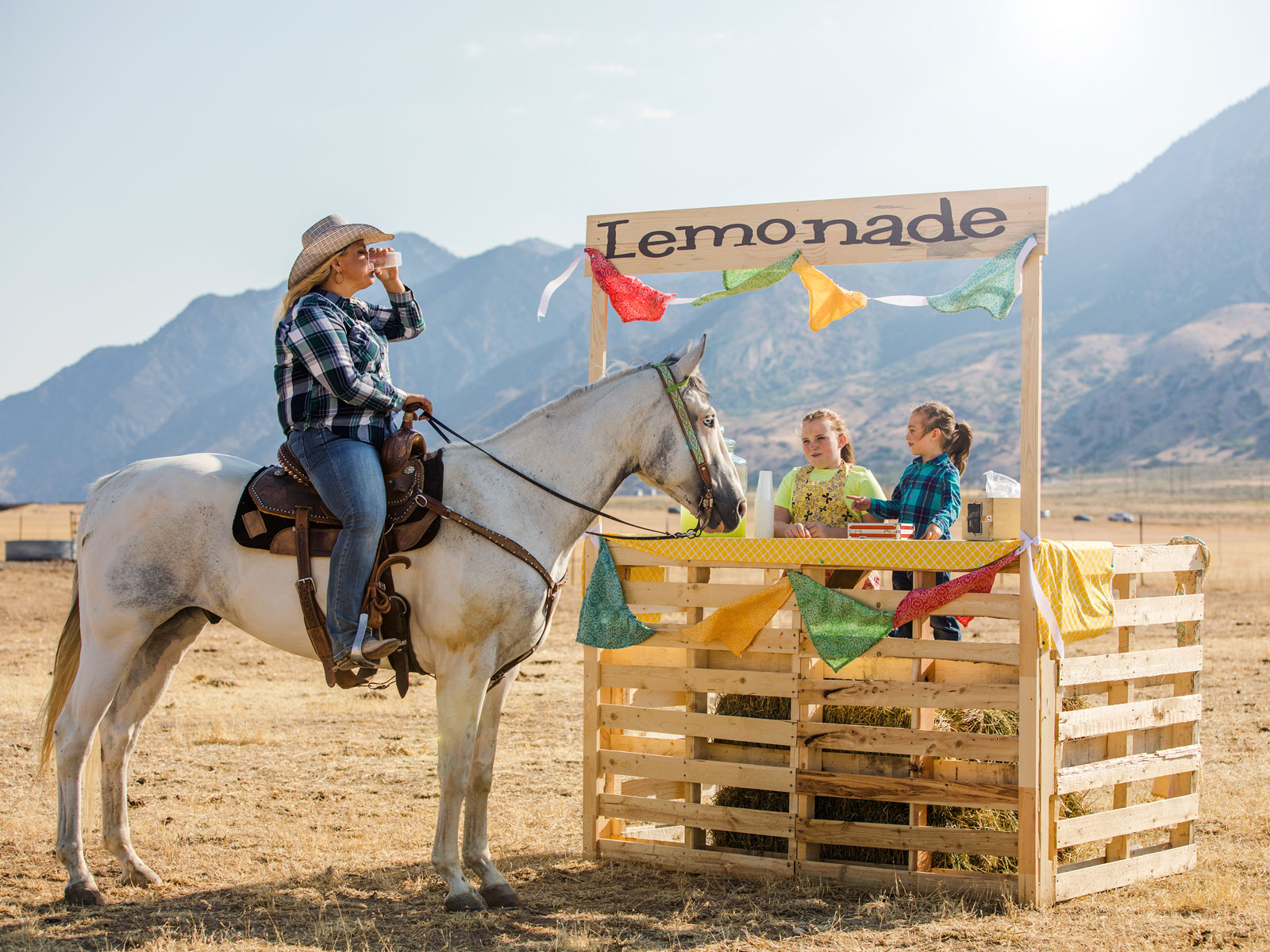 A woman on a horse in front of a lemonade stand with mountains in background