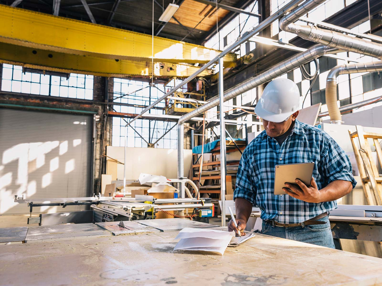 Man in hardhat reviewing orders on a clipboard in a warehouse