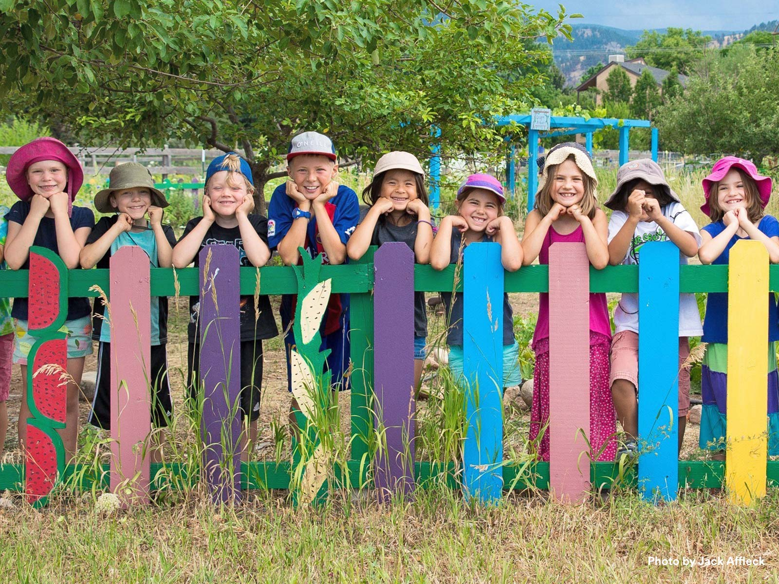 Children smiling leaning on a colorful painted fence in front of a playground