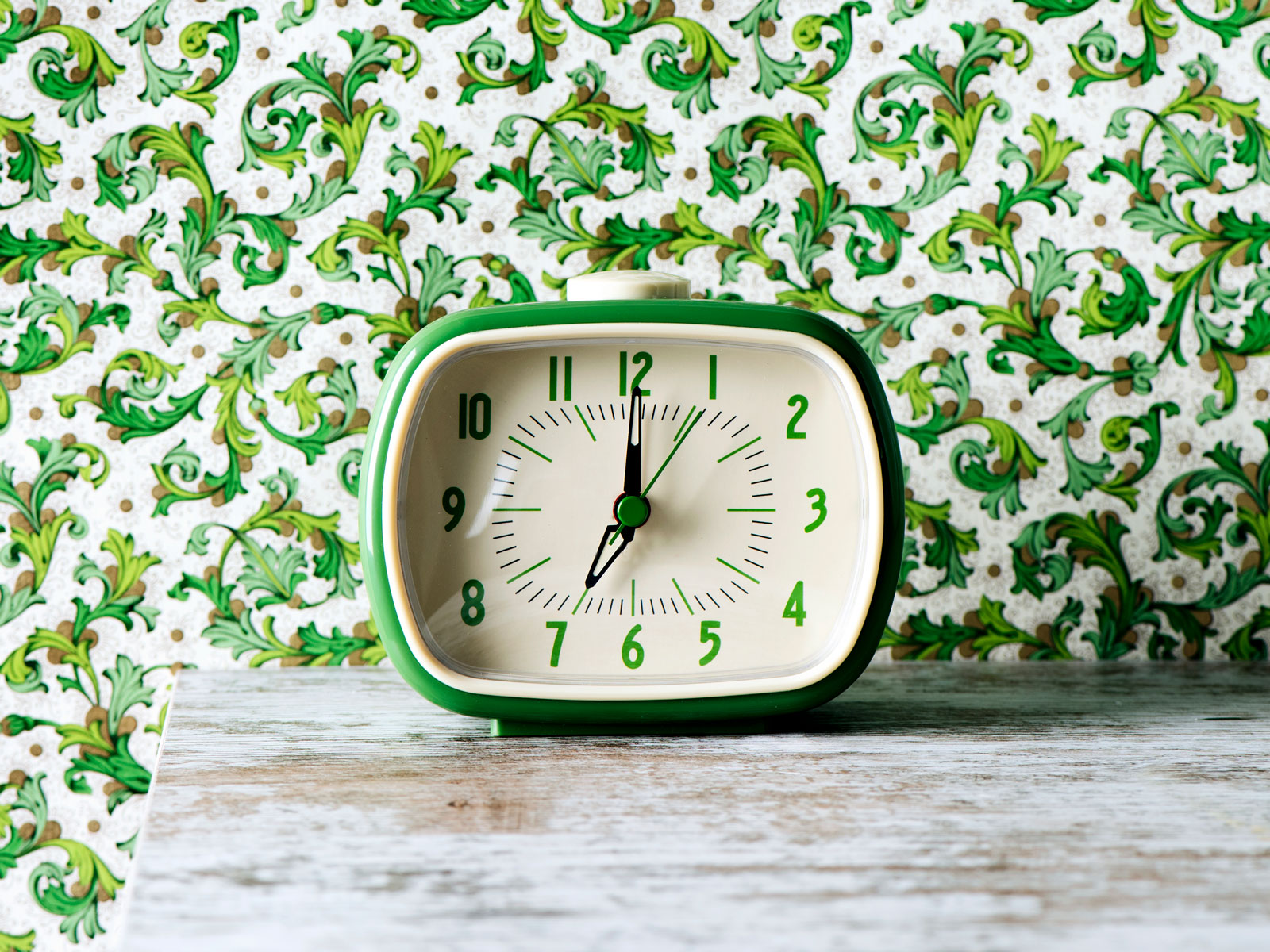 A green clock in front of a green floral print wallpapered wall - horizontal layout