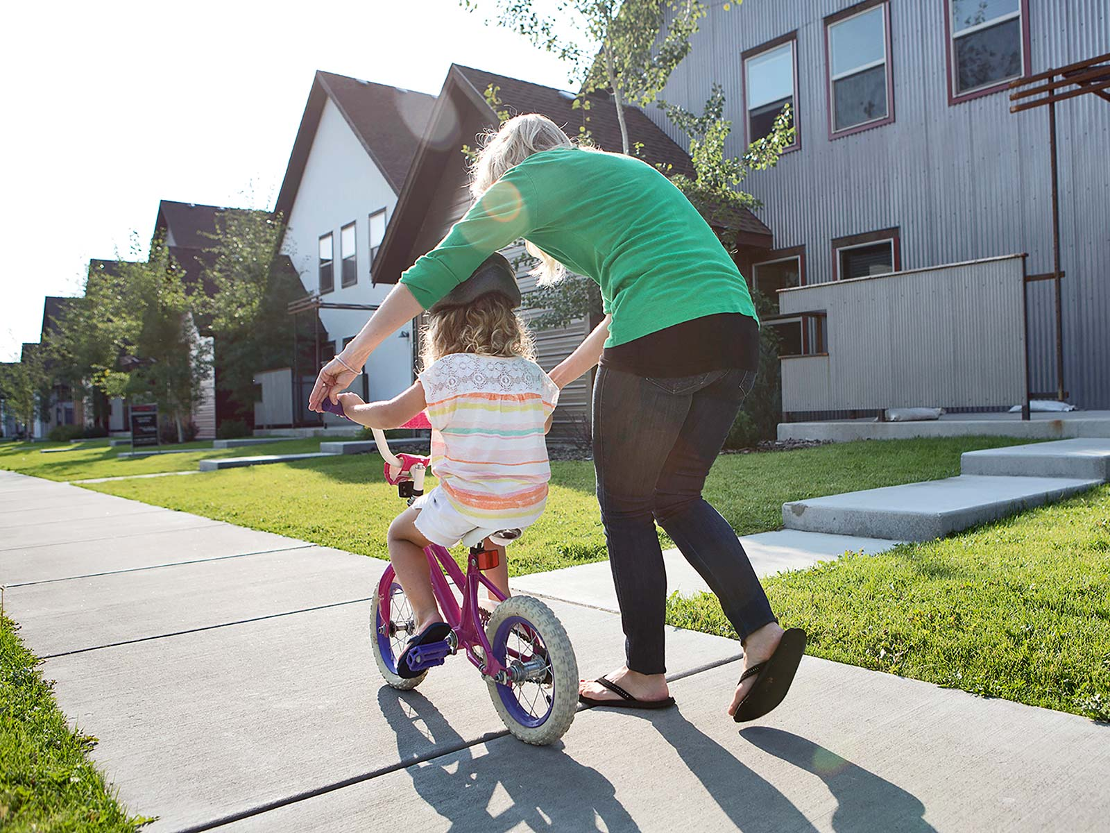 Mother teaching daughter to ride a bike in front of their home