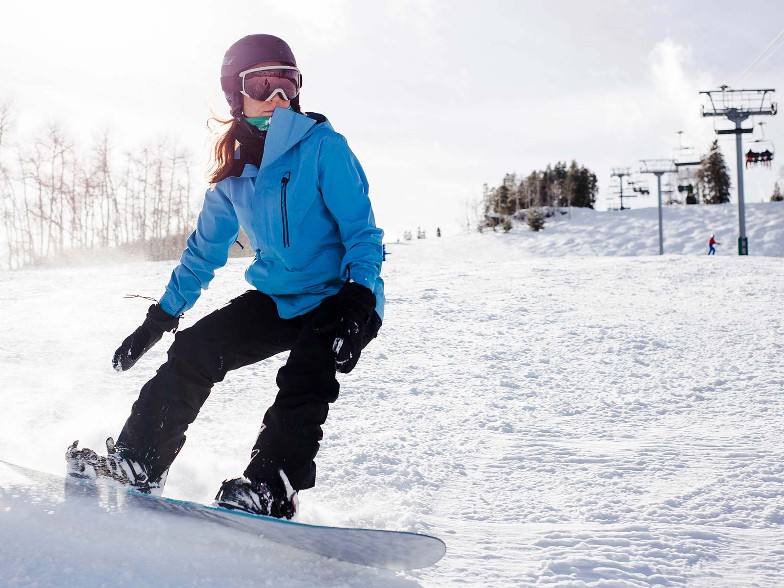 Cool female snowboarder carving down a snowy slope