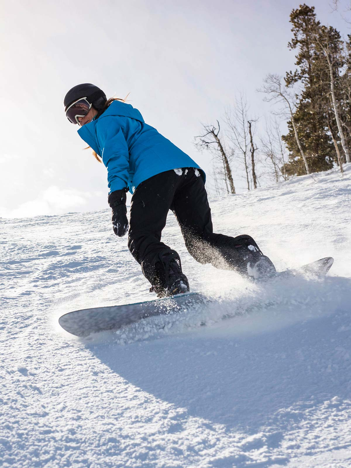 Woman in a blue jacket snowboarding down a slope