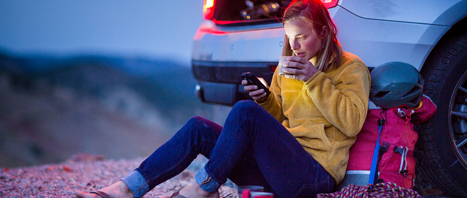 Camping woman leans back on the bumper of her car, looking at her phone and sipping a hot beverage