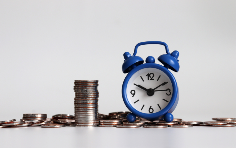 Photo of an alarm clock on a pile of loose change
