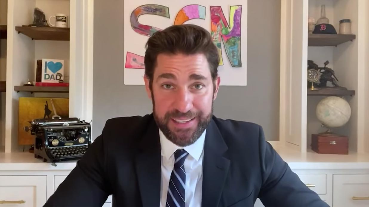 John Krasinski in a suit at home, hosting Some Good News