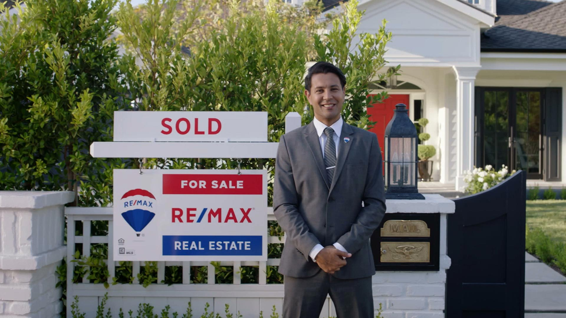 "A real estate agent standing in front of a house with a RE/MAX ""Sold"" sign"