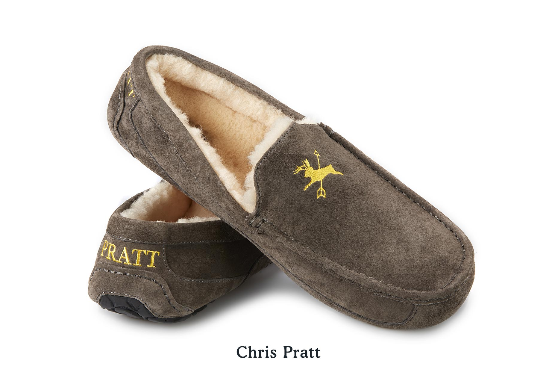 "A pair of UGG Slippers for Chris Pratt with embroidery of a deer crossed with an arrow and the name ""Pratt"" on the heel"