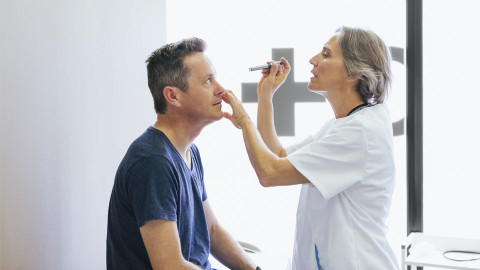 Man getting eye checked by Doctor with a torch