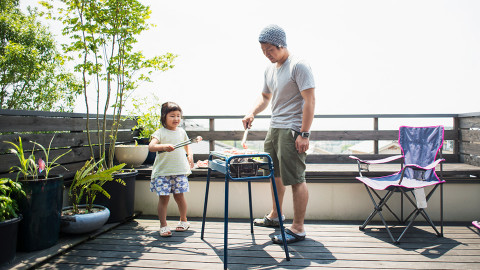 Man cooking barbeque with daughter on balcony