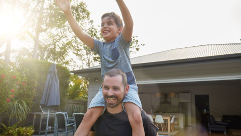 A dad with his son sitting on his shoulders in a family backyard