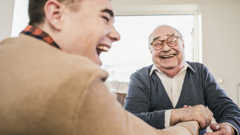 A elderly man laughing at a table with his relative