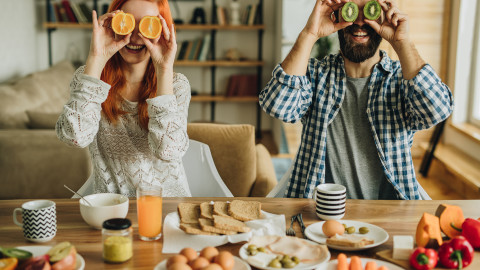 a couple eating breakfast and holding fruit up to their face