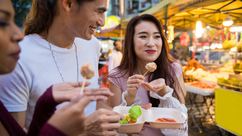 Man and Woman eating exotic street food outdoors