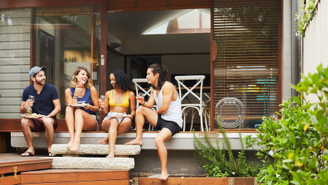 four people sitting on the verandah, chatting with food and drinks