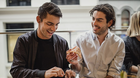 Young men enjoying a healthier pizza alternative