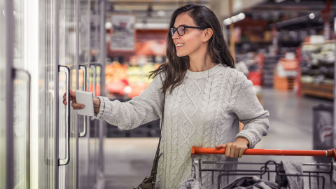 Woman with trolley shopping at supermarket