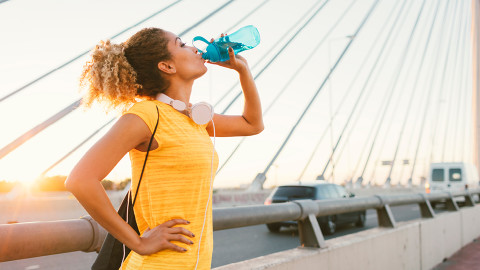 brunette woman in yellow top walking along bridge drinking from reusable water bottle