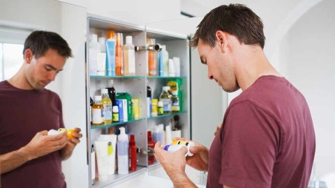 A man comparing information on two containers of medicine in front of an open medicine cabinet.