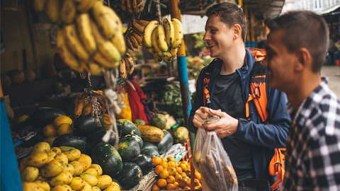 Young travellers saving money by shopping for fruit at local market