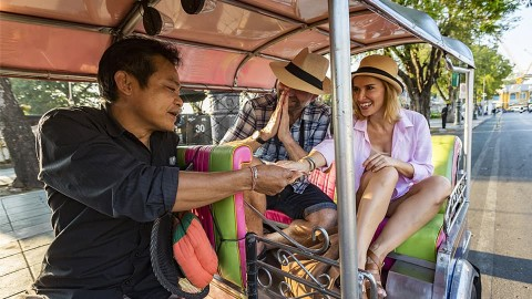 Young couple overseas travelling in cab to save money