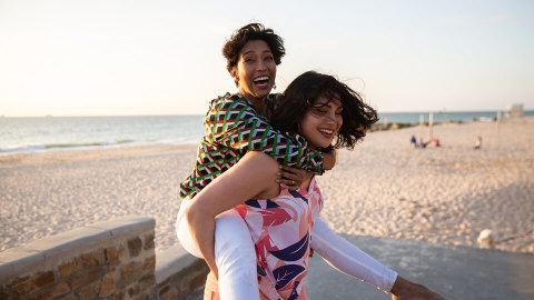 One woman piggybacking another woman by the beach