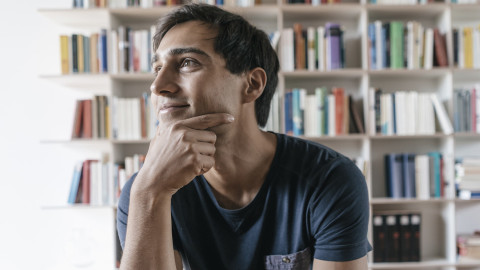 Man sitting in front of bookcase thinking