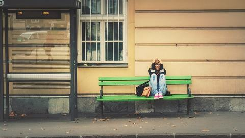 Young girl on bench with head in hands experiencing a quarterlife crisis