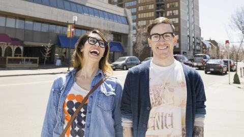 A couple walking on the street both wearing glasses