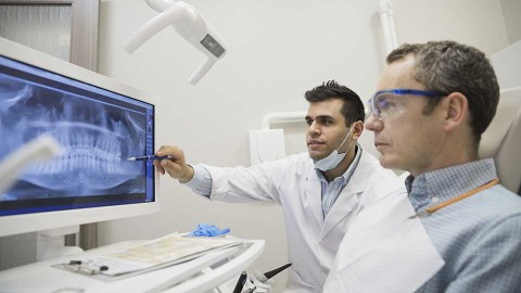 Man and his dentist reviewing x-rays of his mouth to review if he needs to have his wisdom teeth removed.