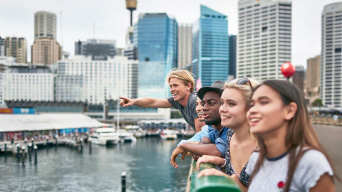 A group of friends standing on a bridge and looking at Sydney Harbour