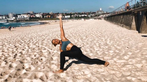 woman on the beach in a lunge yoga pose with left arm extending to the sky