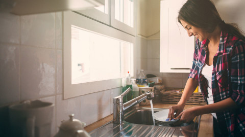 A woman washing up dishes in a sink