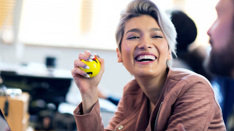 A woman laughing and squeezing a stress ball