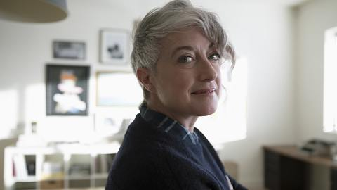 woman with grey hair posing in living room looking at camera