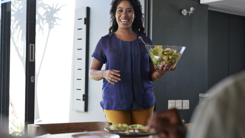 A woman carrying a bowl of salad to a dining table
