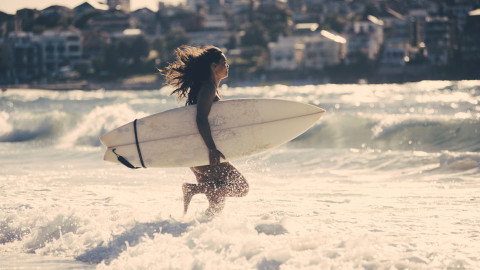 Young woman balancing her lifestyle and heading into the ocean for a surf