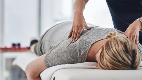 A woman face down on a massage bed with a masseuse pushing into her back.