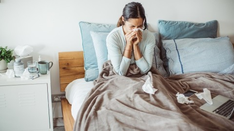 A woman unwell with the flu in bed blowing her nose on tissues