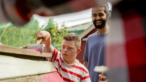 Young bearded man volunteering with a young boy local community charity