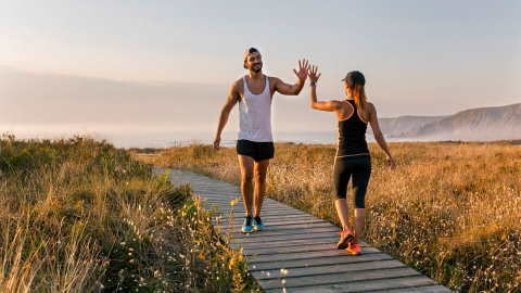A man and woman celebrating the completion of their run on an outdoor boardwalk