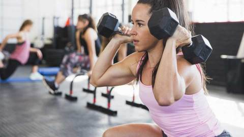 A woman lifting dumbbells at a gym