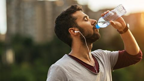 young man who's just finished a marathon run drinking from a water bottle