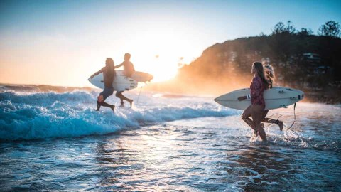 Four people running into the ocean with surfboards
